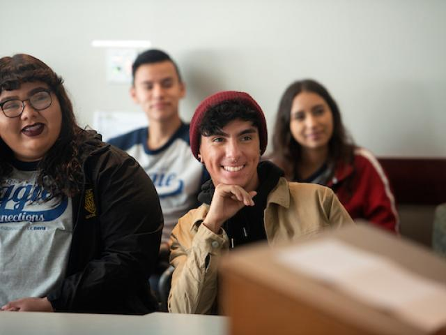 Students smile and listen in a lecture.