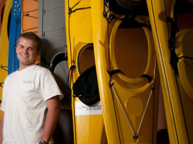 A male student stands in front of a stack of colorful kayaks