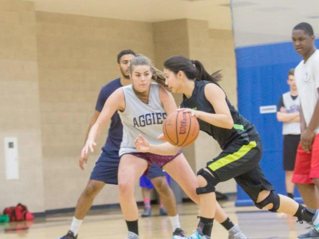 A female student competes in a coed rec sports basketball game