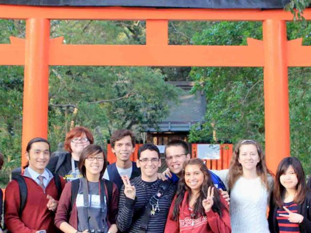 UC Davis students pose in front of a shinto shrine in japan.