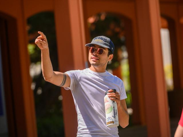A tour guide pointing out a UC Davis campus landmark