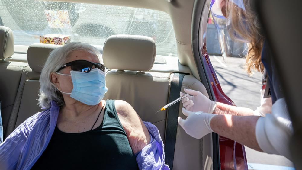Woman sitting in car receives vaccine.