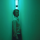 A man standing in Nauman's Blue and Yellor corridor.
