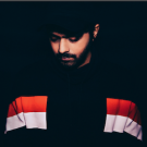 Jai Wolf looking downward, wearing mostly black and standing in front of a black background.
