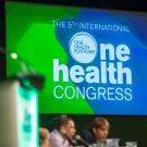 One Health Congress logo on a presentation screen behind event speakers.