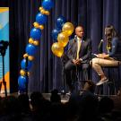 Chancellor Gary S. May at the mike with two students hosting a podcast