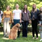 Assistant Professor Gwen Arnold, flanked by some of her students, in a line facing the camera, with Doug the Dog next to Gwen