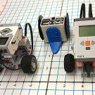 Three small robots, two on wheels, sitting on a paper grid