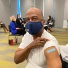Chancellor Gary S. May, in mask, rolls up sleeve to show bandage over innoculation.