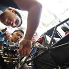 Three students adjust gears on a racecar frame that they designed