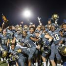 Football players celebrate and pose with the Golden Horseshoe trophy.