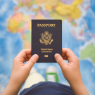 A person holds U.S. passport against backdrop of world map.