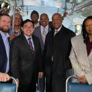 Chancellor Gary S. May amid group of people on historic bus