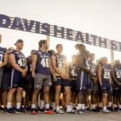 "Student-athletes stand under new ""UC Davis Health System"" sign while Chancellor May talks at podium."