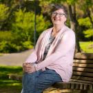 Dean Lauren Lindstrom, casually sitting on bench in the arboretum.