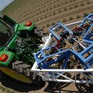 Large tractor pulls frame-like equipment with cameras through tomato field.