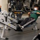 Man wearing face covering uses rowing machine at the ARC.