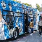 A bus decorated with photos of UC Davis athletes.