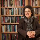 Suad Joseph, sitting at table, hands folded, in front of bookcases.