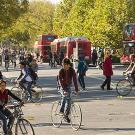 Scene at the UC Davis campus street with many bikes and double-decker buses in the background