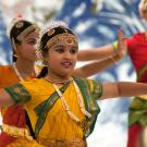 A group of young women preform a South Asian style dance