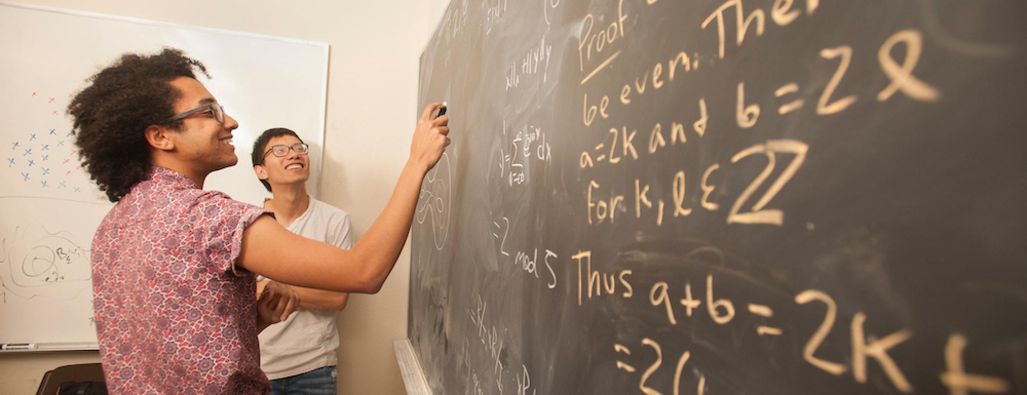 A student does equations at a blackboard.
