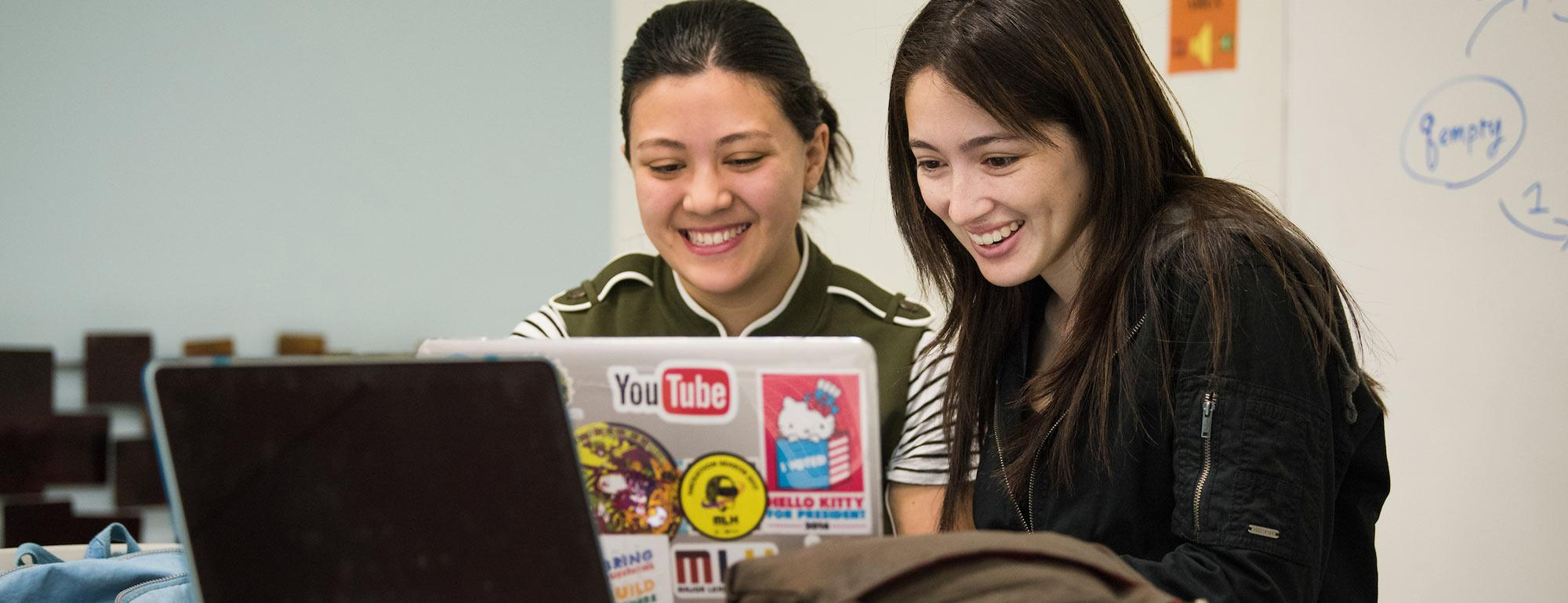 Two female students share a laptop to evaluate their work.