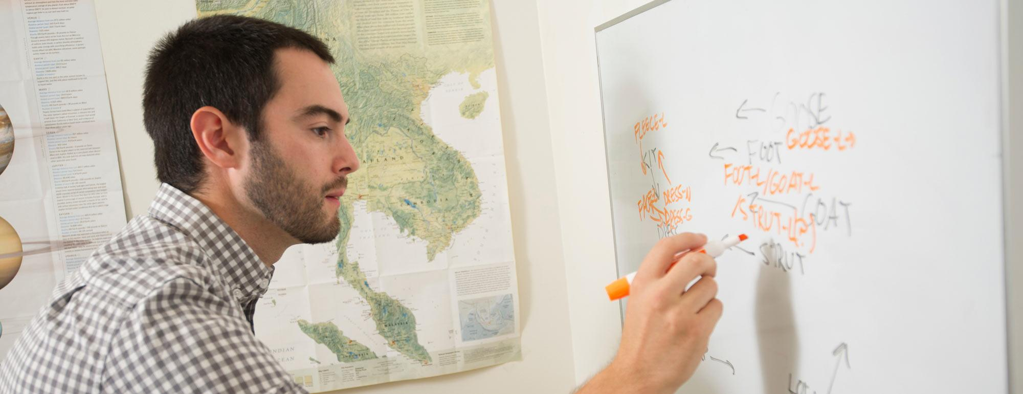 A PHD candidate evaluates word structure on a whiteboard