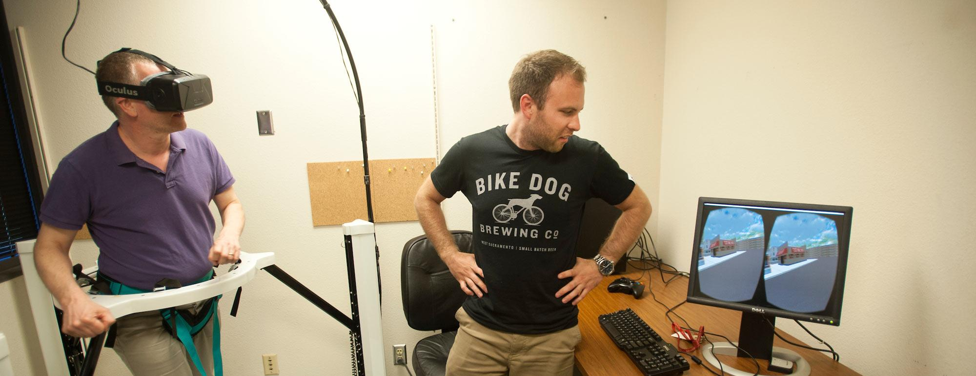 A test subject uses a haptic treadmill will a researcher observes his virtual actions