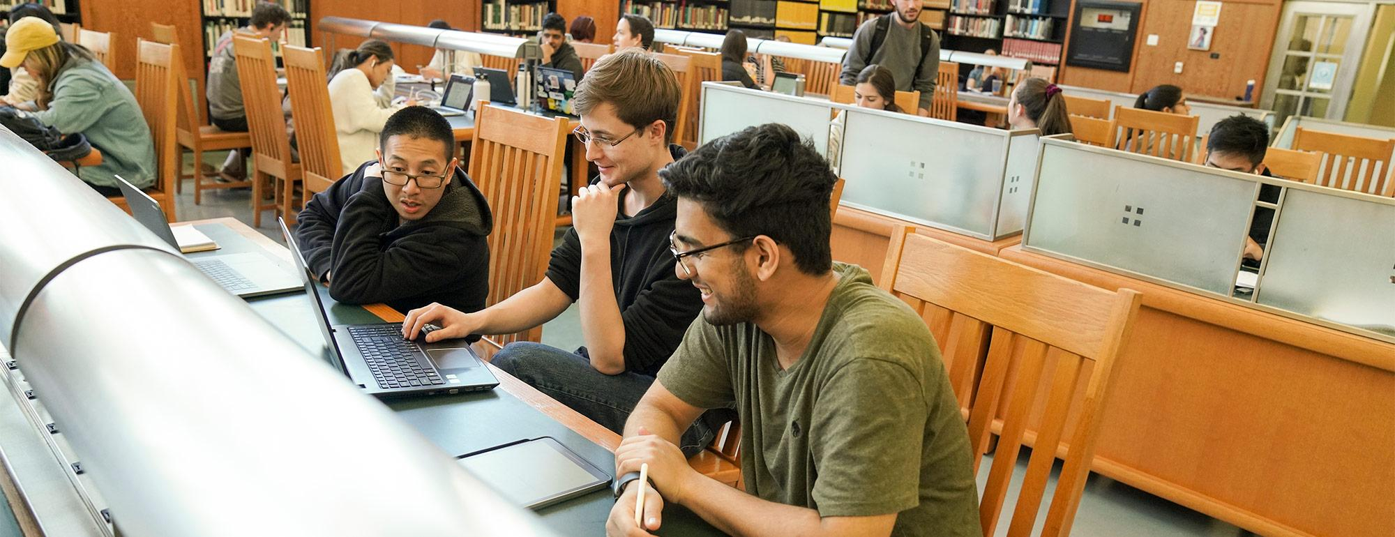 three students working on project together in the Shields Library.
