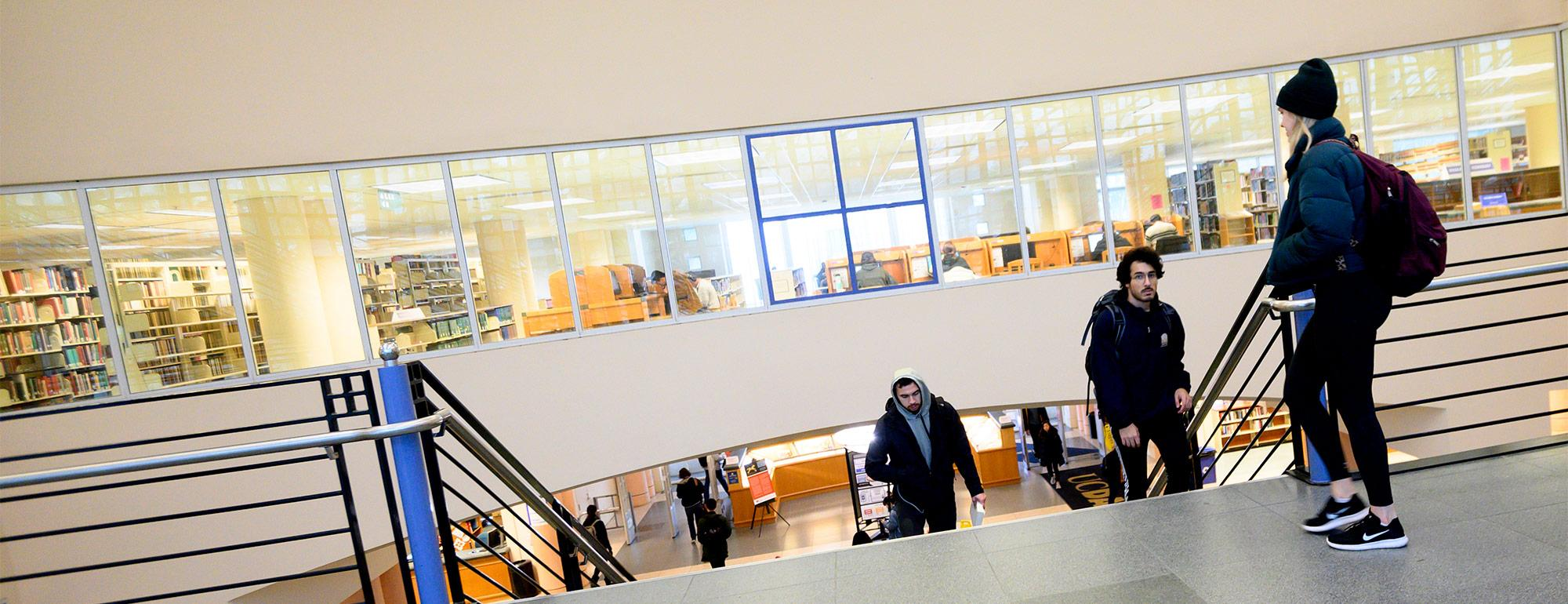 Two students walking up the stairs as another is heading down at the Shields LIbrary.