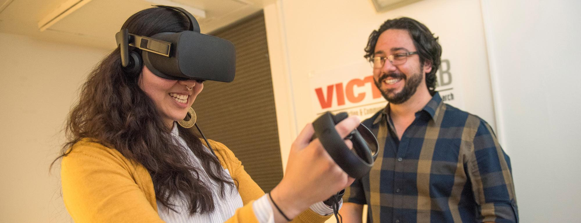A student smiles while using a virtual reality set up.