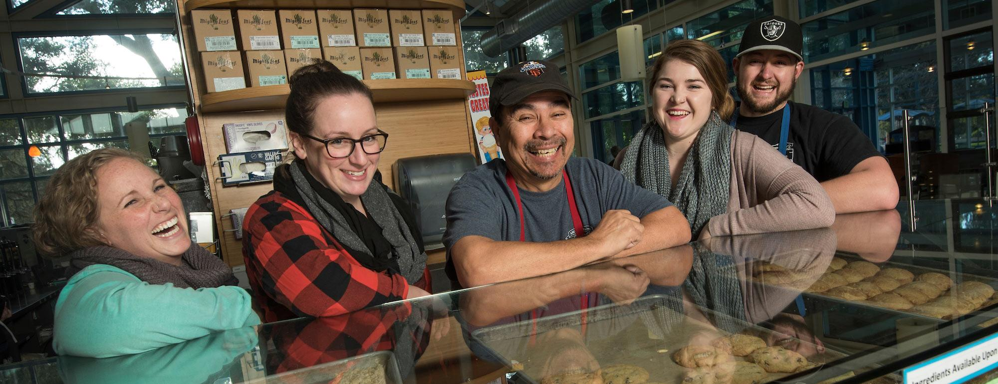 Student Coffee House workers smile with their manager over a counter filled with baked goods