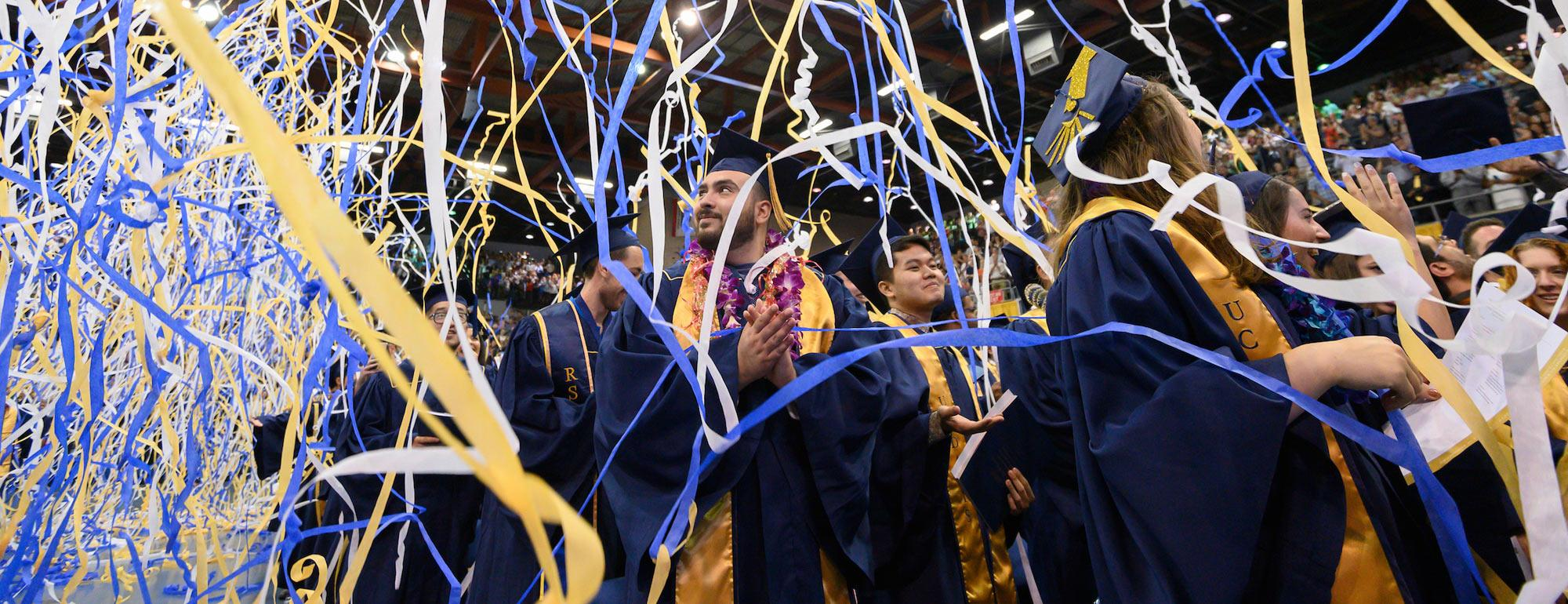 Students celebrating at commencement while streamers fall from the ceiling