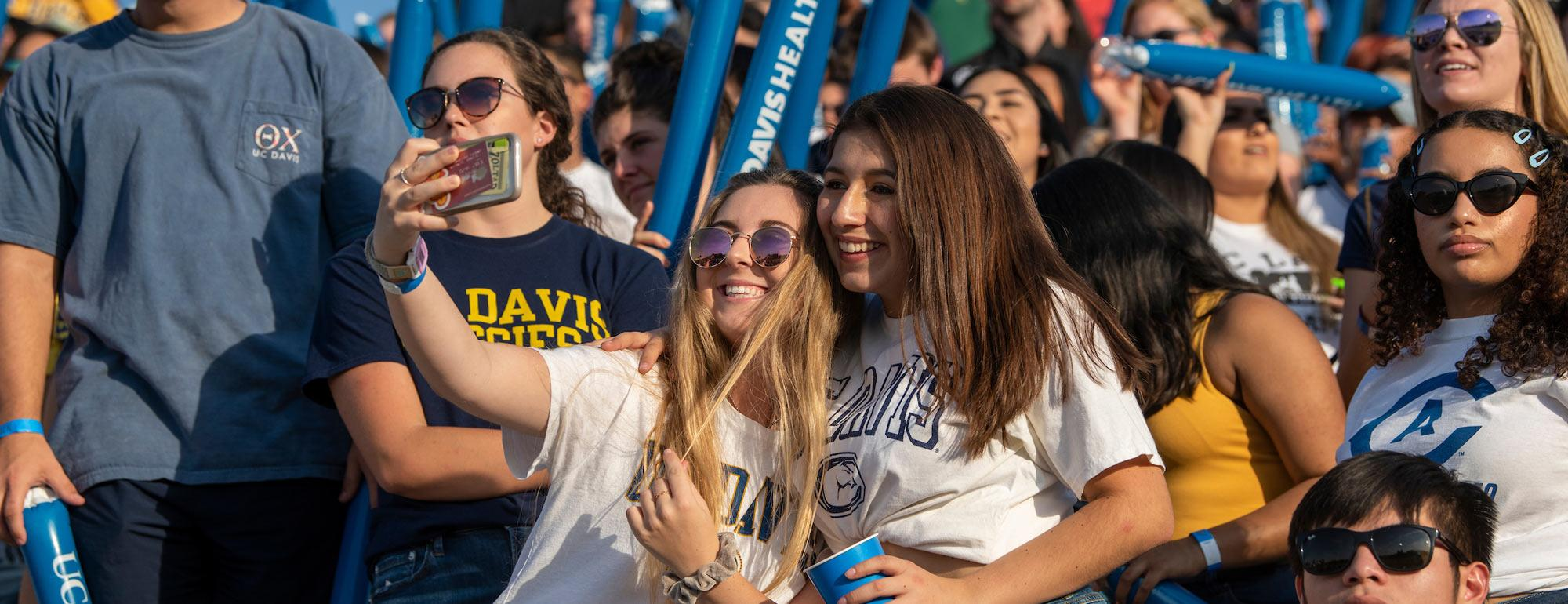 Two female students share a selfie in the crowd of a UC Davis football game.