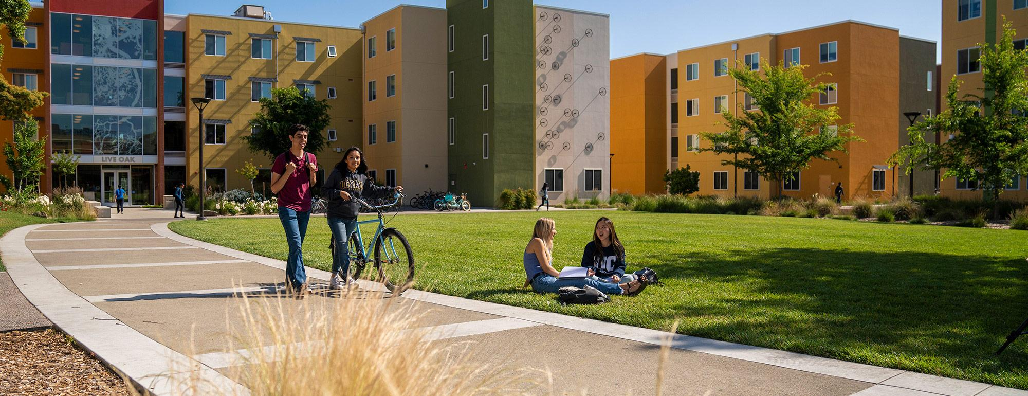 two student walking a bike while two more students are sitting on the grass in front of the residence halls