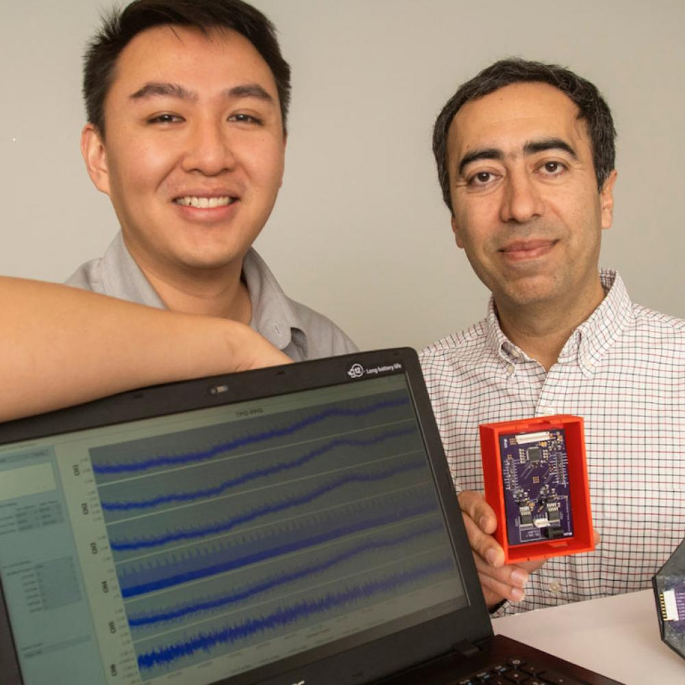 A student and professor pose next to their computer engineering project