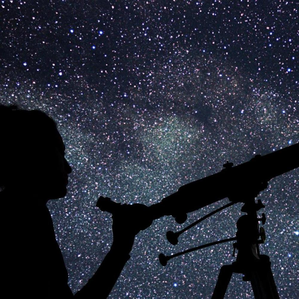 A person looking up at the stars through a telescope