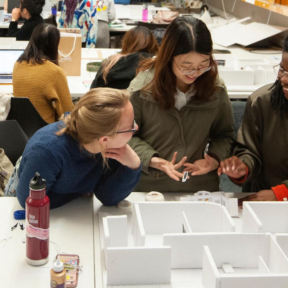 Three female students discussing a design model
