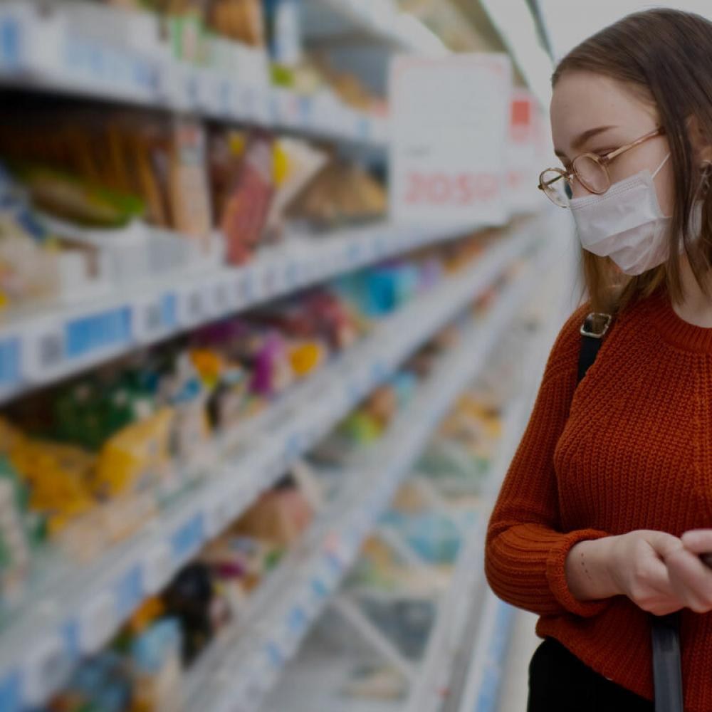 girl shops while wearing breathing mask