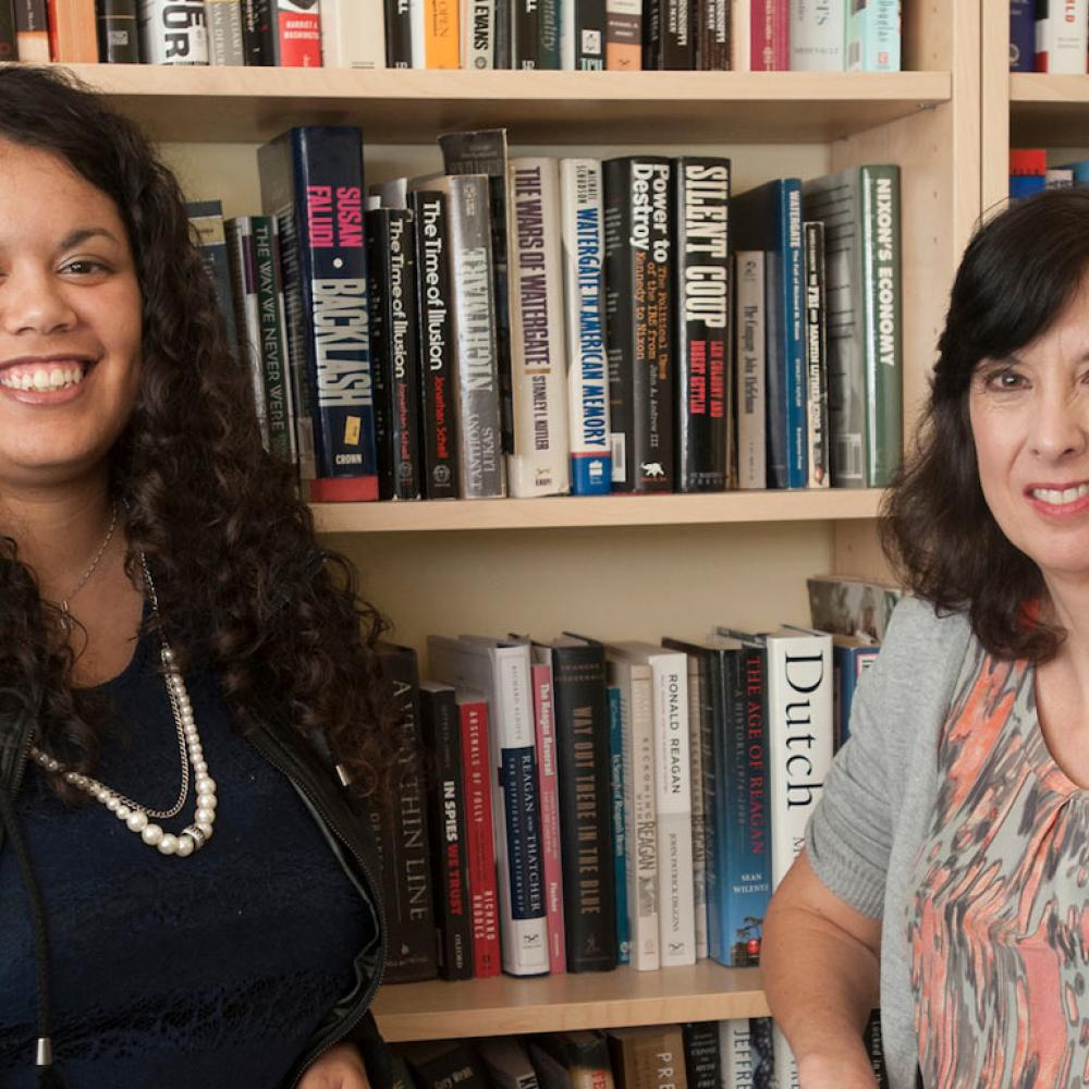 A PHD candidate and a History professor pose in front of a book shelf.