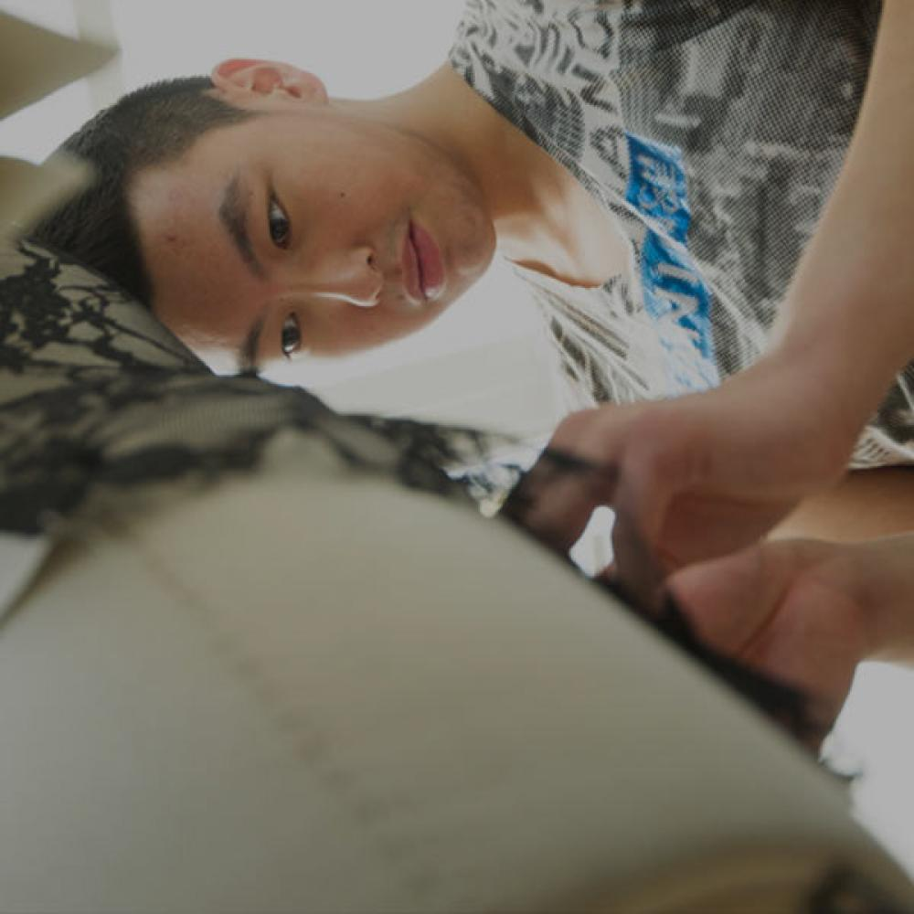 A male student puts the finishing touches on a garment he is designing for the Picnic Day fashion show