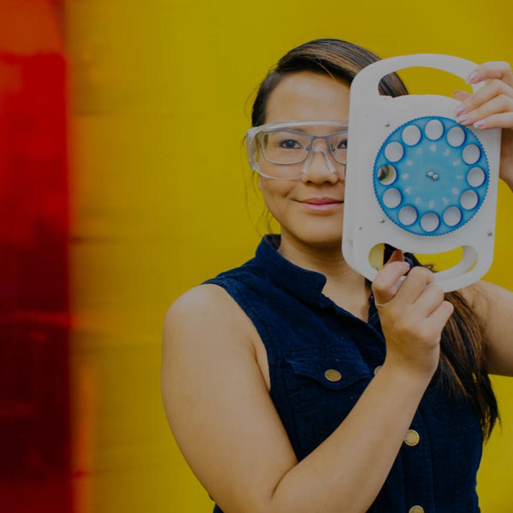 A student holds up portable eye examination technology that she invented