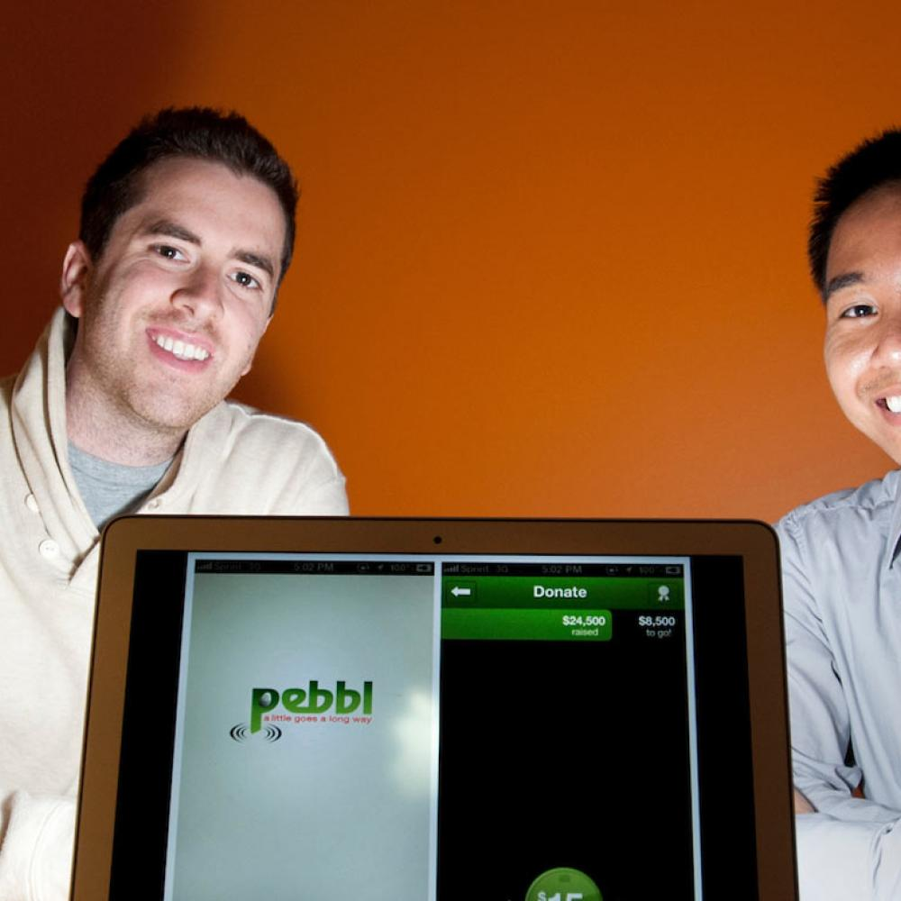 Two Graduate students pose with a laptop that shows the app that they created.