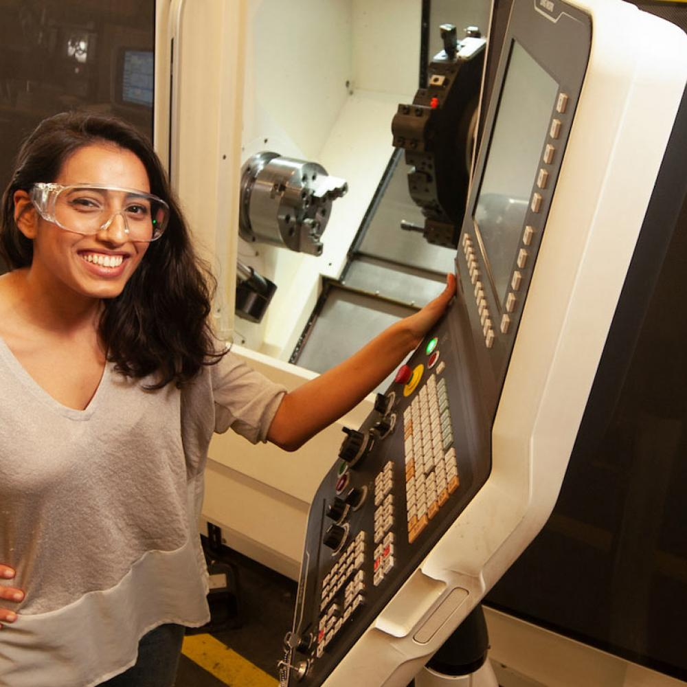 A female student in safety glasses exhibiting some machinery