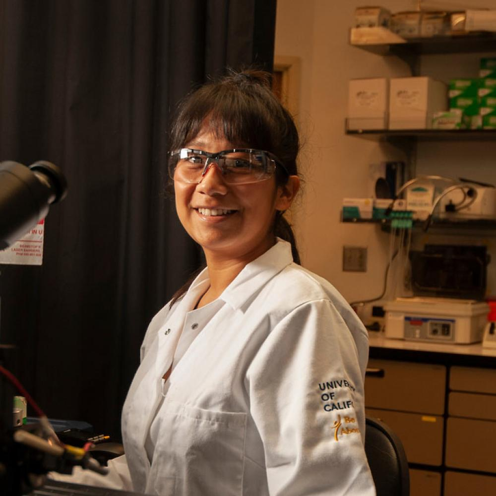 A female researcher smiles in her lab