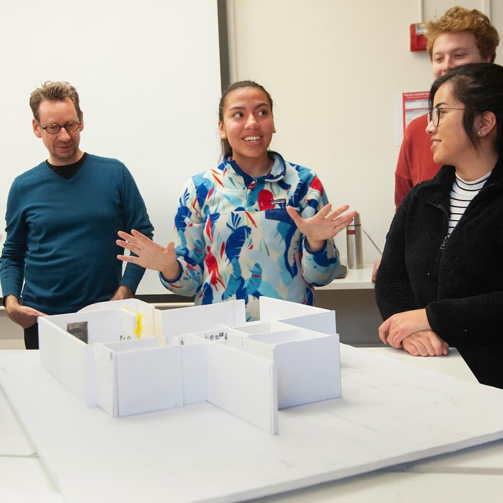three students and a professor looking at a model of a building in a design class.