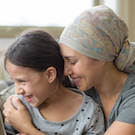 woman with cancer holds her 8 year old daughter