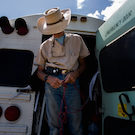 UC Davis researcher Eric Davis ties some rope outside his mobile veterinarian school bus in the Dakotas