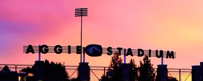 The entrance gate of Aggie Stadium against a sunset
